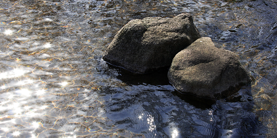 An image of two large rocks side-by-side stationed in running water.