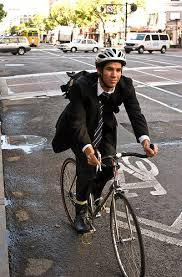 Man in a business suit on a bicycle.