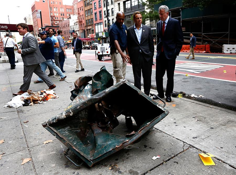 New York Mayor Bill de Blasio (right) and New York Governor Andrew Cuomo stand in front of a mangled dumpster while touring the site of the explosion. Pool / Pool