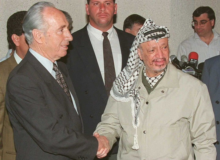 Then-Foreign Minister Shimon Peres (left) and Palestinian Liberation Organization Chairman Yasser Arafat shake hands in 1995 after announcing an agreement on extending Palestinian autonomy on the West Bank.